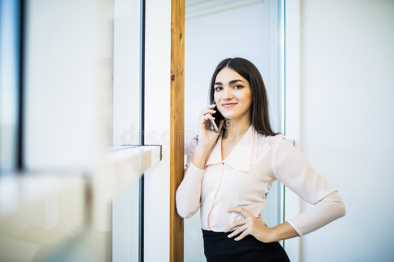 Business talk. Confident young businesswoman in suit talking on the mobile phone and smiling stock images