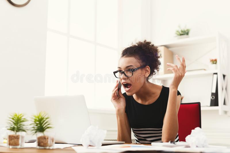 Business talk, furious woman talking on phone at office. Young furious african-american woman talking on phone at modern office copy space. Business consulting stock photo