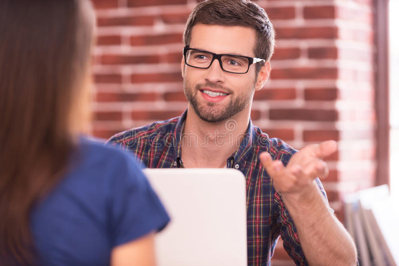 Business talk. Two business people in casual wear talking and smiling while sitting face to face at the table stock photos
