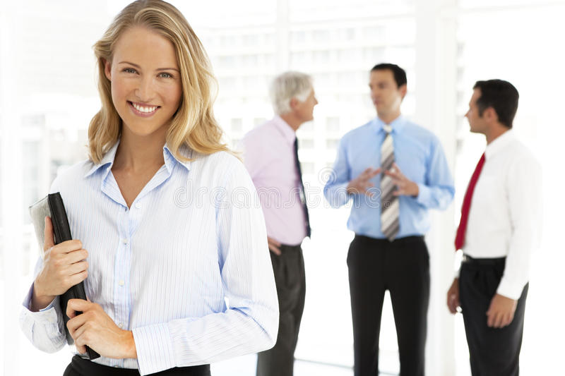 Business Talks. Portrait of a happy businesswoman. Three business people stand and talk in the background. Selective focus on the women on foreground stock photography
