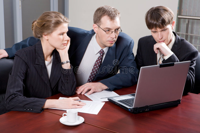 Business team. Of three professionals looking at monitor of laptop in the office royalty free stock photos