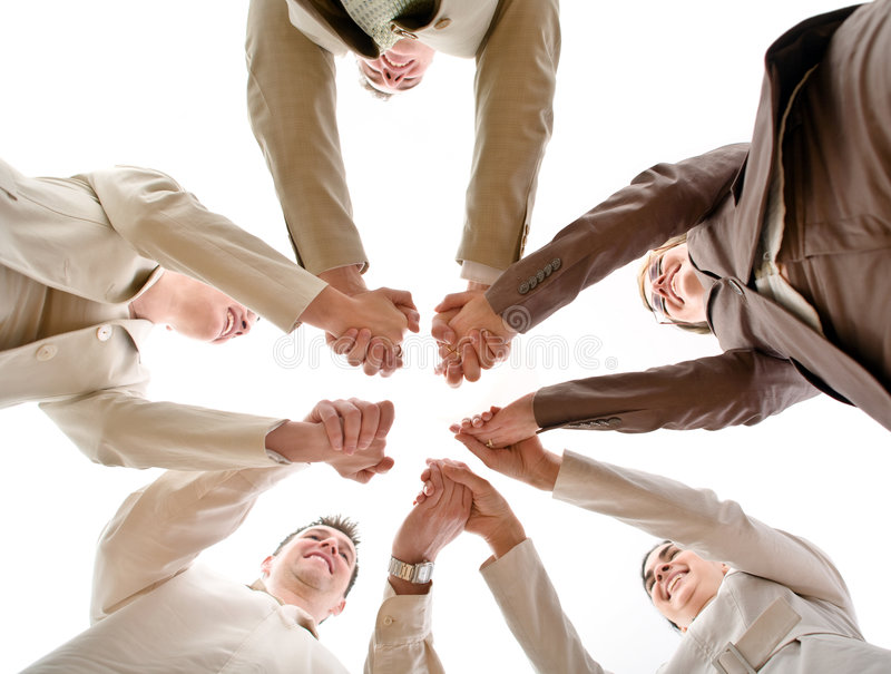 Business Team. Five business people forming a circle and holding hands, smiling, low angle view stock photo