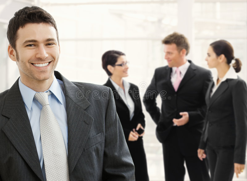 Business team. Standing in office lobby. Happy businessman in front, smiling and looking at camera, others talking in the background stock images