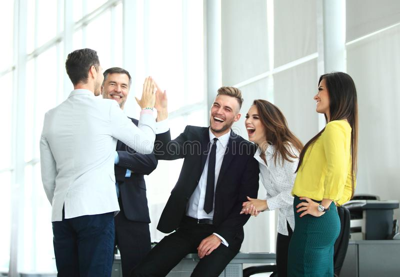 Happy successful multiracial business team giving a high fives gesture as they laugh and cheer their success. Business Team Achievement Success Mission Concept stock photography