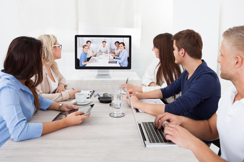 Business team attending video conference. At desk in office