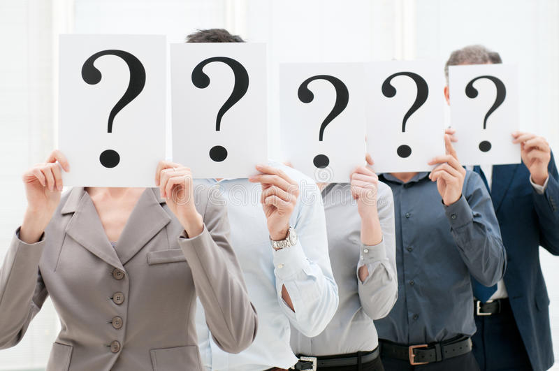 Business team behind question marks. Group of business people hiding their faces behind a question mark sign at office royalty free stock photo