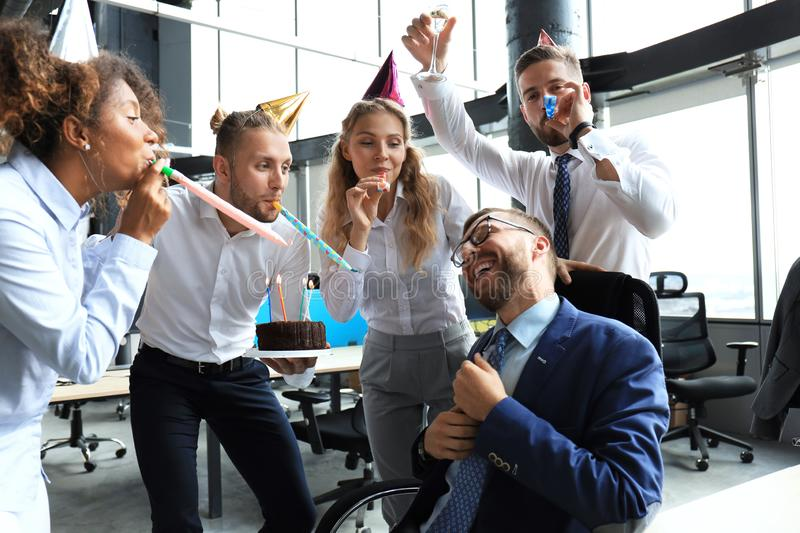 Business team celebrating a birthday of collegue in the modern office.  stock images