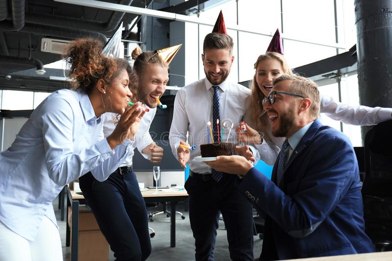 Business team celebrating a birthday of collegue in the modern office.  royalty free stock photography