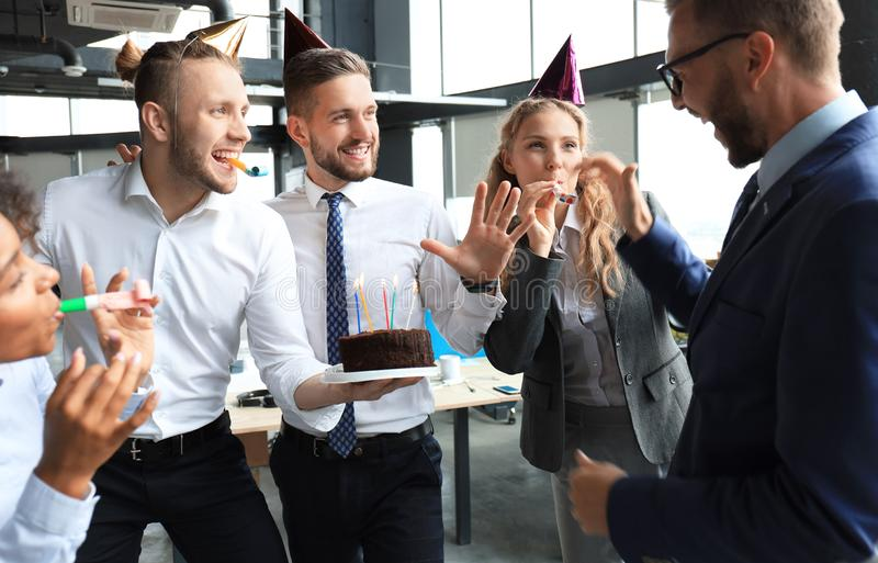 Business team celebrating a birthday of collegue in the modern office.  royalty free stock image