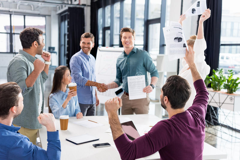 Business team celebrating success together on workplace in office. Young professional group concept stock photo