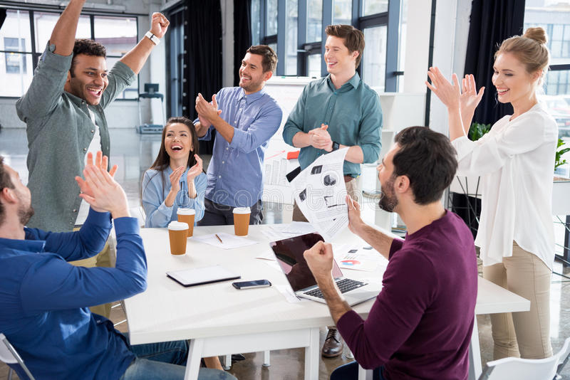 Business team celebrating success together on workplace in office stock image