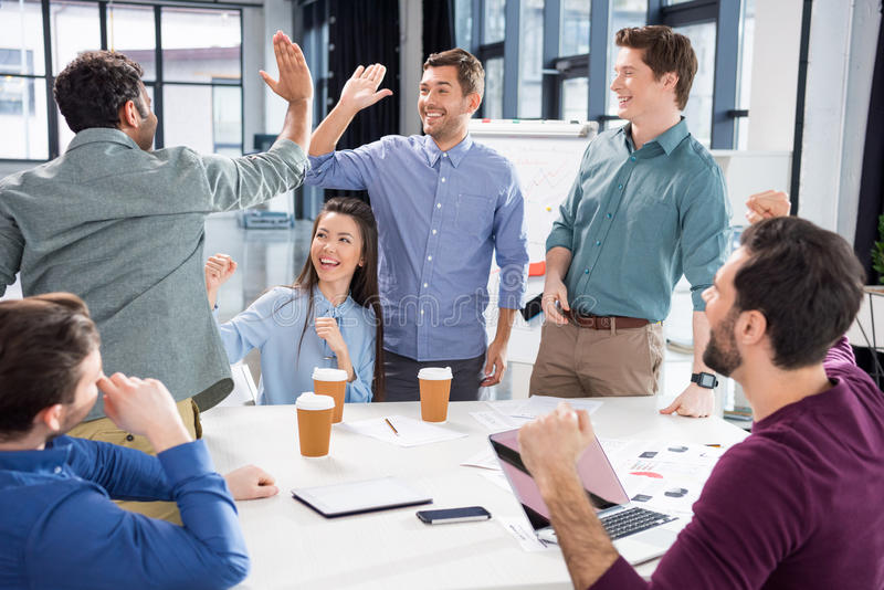 Business team celebrating success together on workplace in office. Young professional group concept stock images