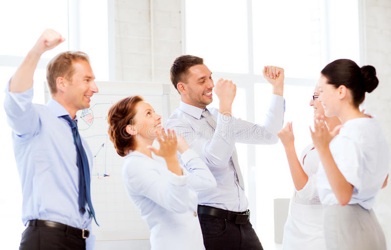 Business team celebrating victory in office. Picture of happy business team celebrating victory in office royalty free stock photography