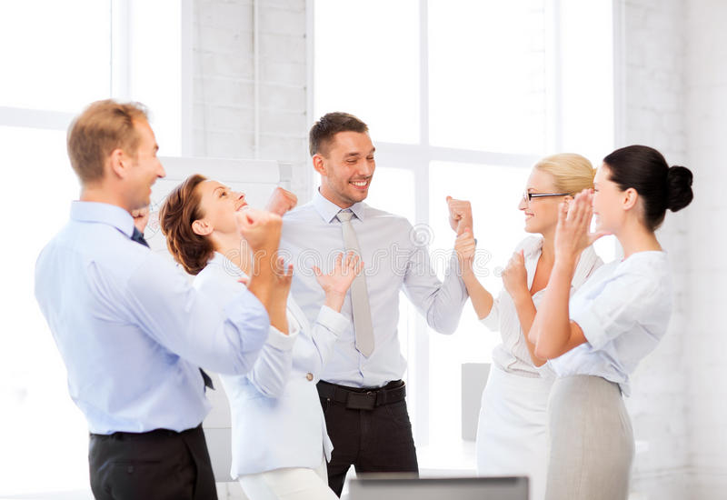 Business team celebrating victory in office. Picture of happy business team celebrating victory in office stock images