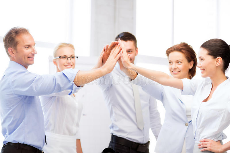 Business team celebrating victory in office. Picture of happy business team celebrating victory in office stock photography