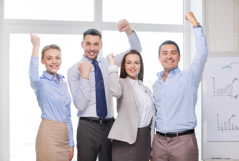 Business team celebrating victory in office. Business, office, success and victory concept - happy business team celebrating victory in office royalty free stock photos