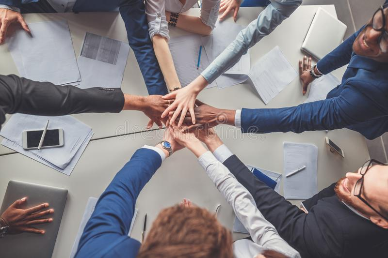 Close-up of people holding hands together while sitting around the desk. Business Team Celebration Party in office Success Concept royalty free stock photography