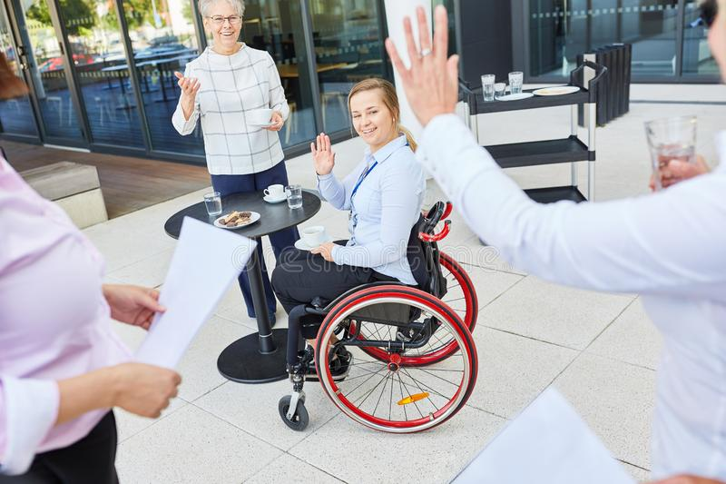 Business team colleagues waving to woman in wheelchair. Business team colleague waving women in wheelchair for greeting and inclusion stock photos