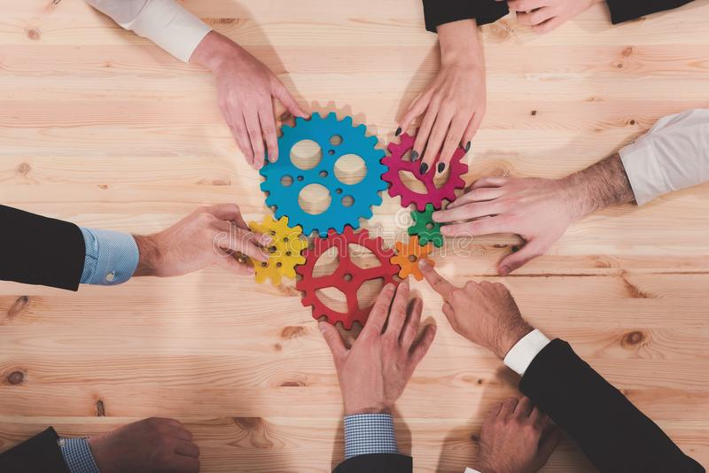 Business team connect pieces of gears. Teamwork, partnership and integration concept. Teamwork of businesspeople work together and combine pieces of gears