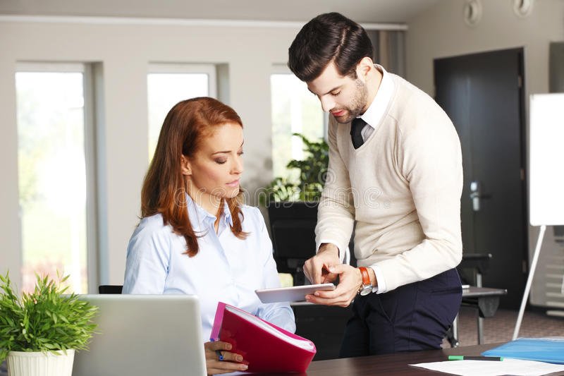 Business team consulting. Portrait of young businessman holding hand digital tablet and consulting with executive businesswoman while sitting at office in front royalty free stock photo