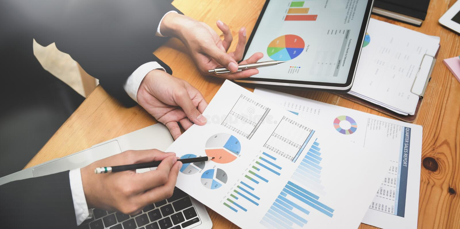 Business team consulting their marketing plan. Professional business team consulting their marketing plan while using charts and graphs in modern office royalty free stock image