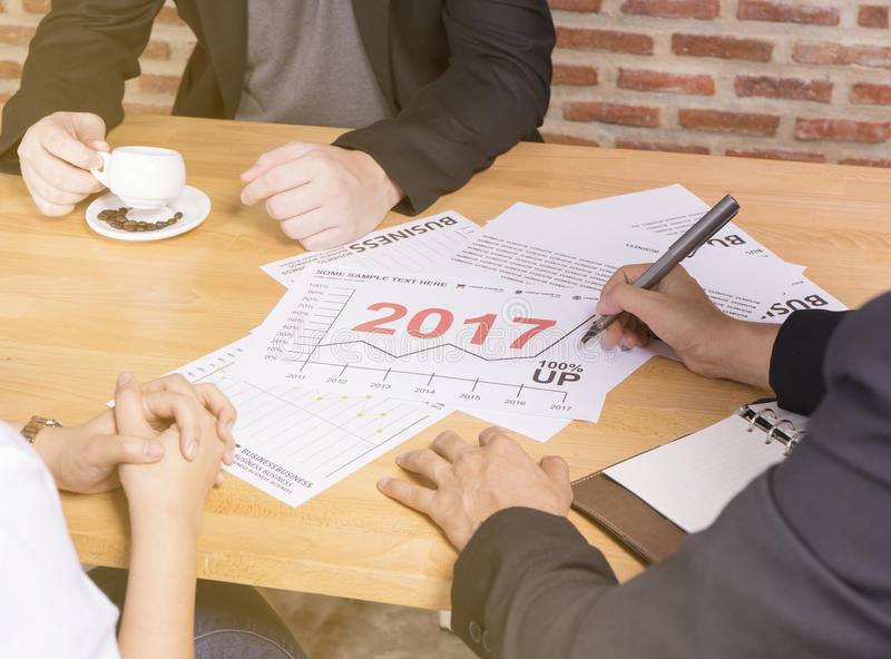 Business team discussing analyze financial report graph year 2017 trend forecasting planning in cafe coffee shop stock photo