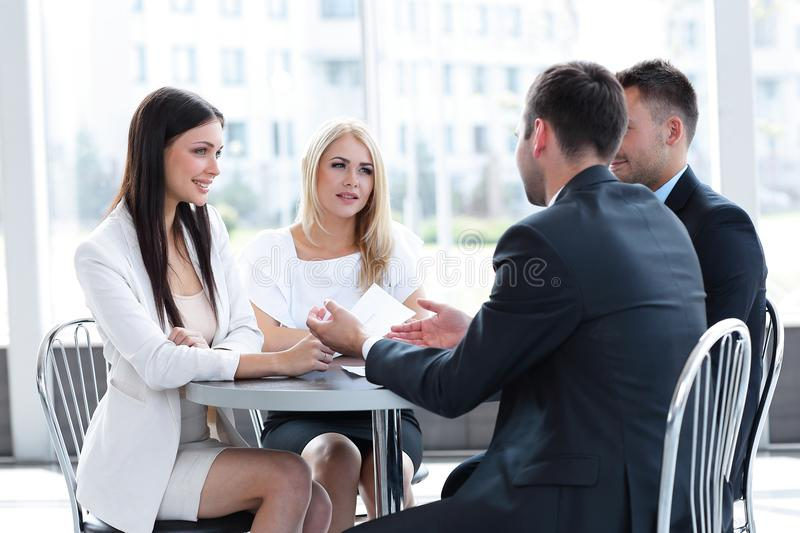 Business team discussing business issues, sitting at a table in a cafe. stock image