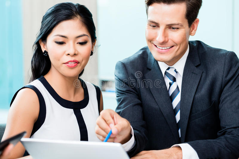 Business team discussing project looking at laptop stock image