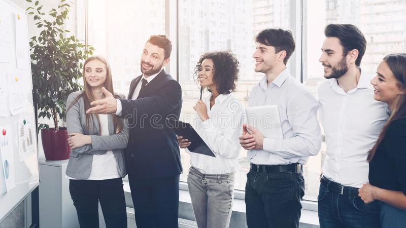 Business team discussing project together, looking at graphics royalty free stock photo