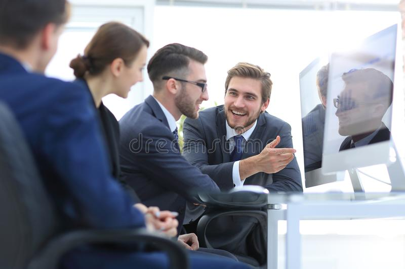 Business team discussing while sitting at their Desk stock images