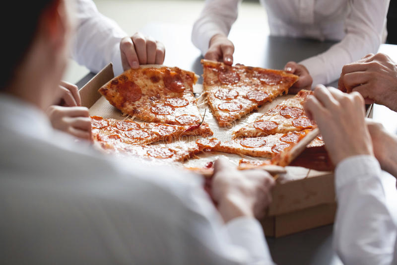 Business team eating pizza stock image