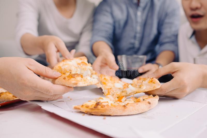 Business team is eating pizza at work while working stock image