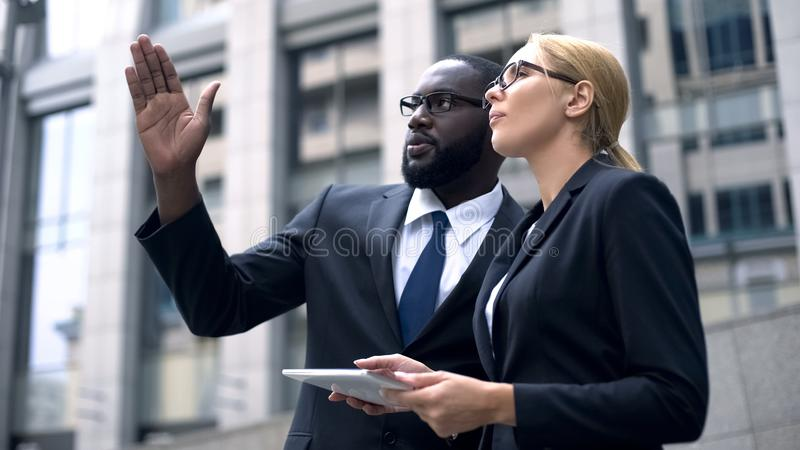 Business team of engineers discussing architectural design, using digital tablet stock photo