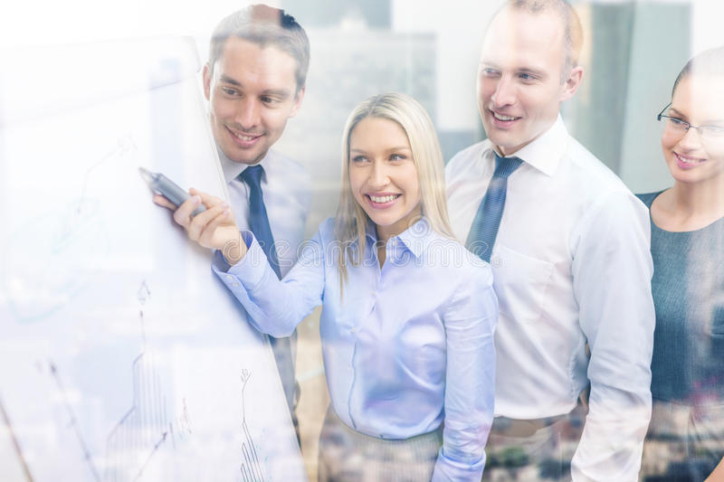 Business team with flip board having discussion. Business and office concept - smiling business team with charts on flip board having discussion stock images