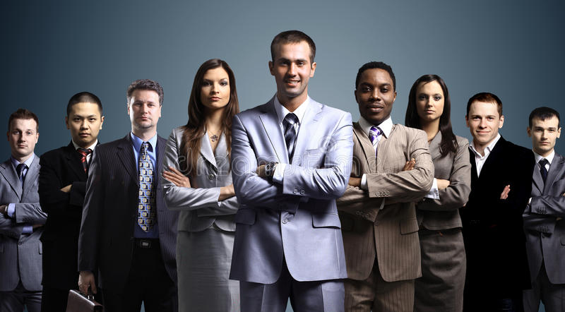 Business team formed. Of young businessmen standing over a dark background