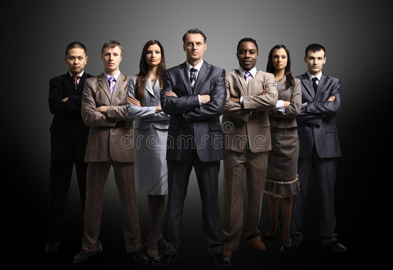 Business team formed of young businessmen. Standing over a dark background royalty free stock photos