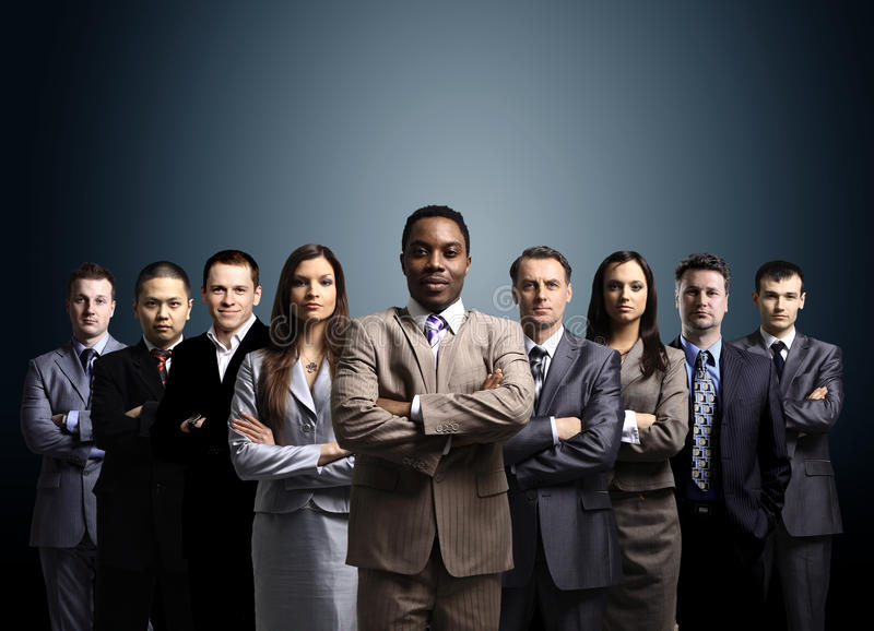 Business team formed of young businessmen. Standing over a dark background royalty free stock image