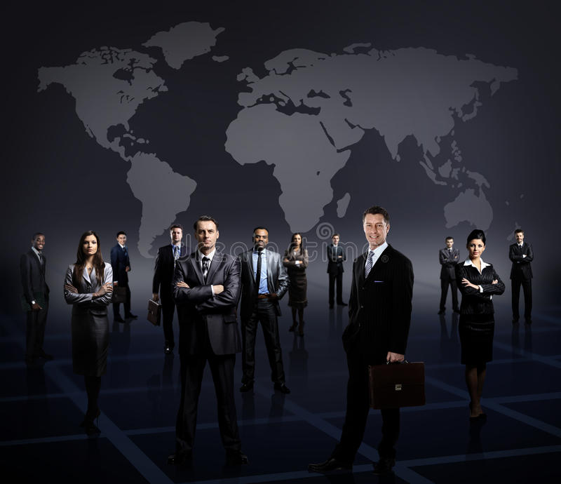 Business team formed of young businessmen standing. Over a dark background royalty free stock photography