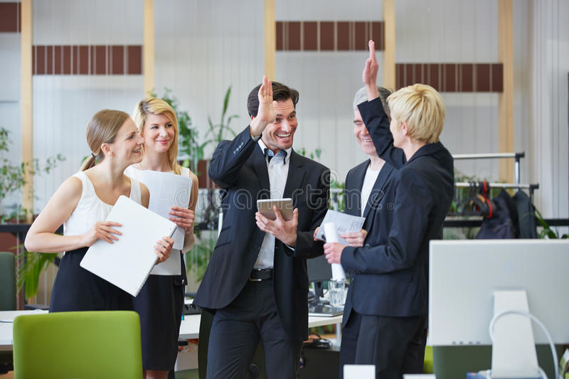 Business team giving high five in office royalty free stock photo