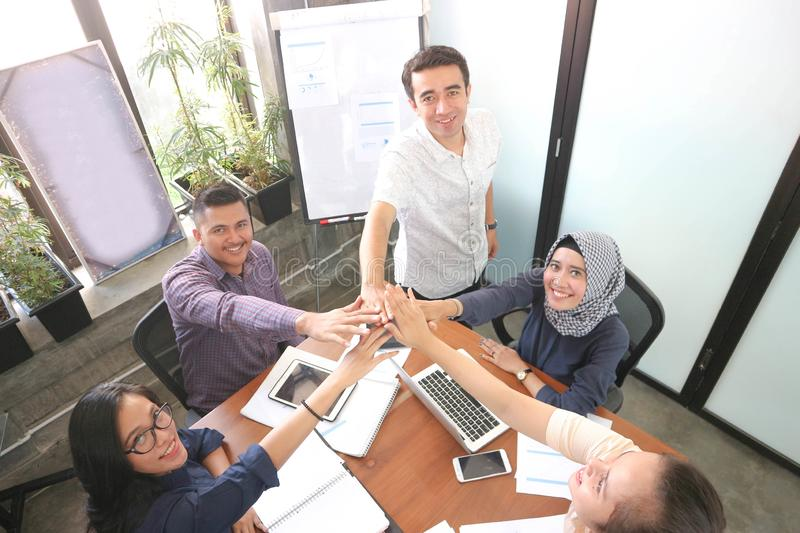 Business team giving highfive together at the office meeting room with laptop smartphone and tablet near windows with white board stock photo
