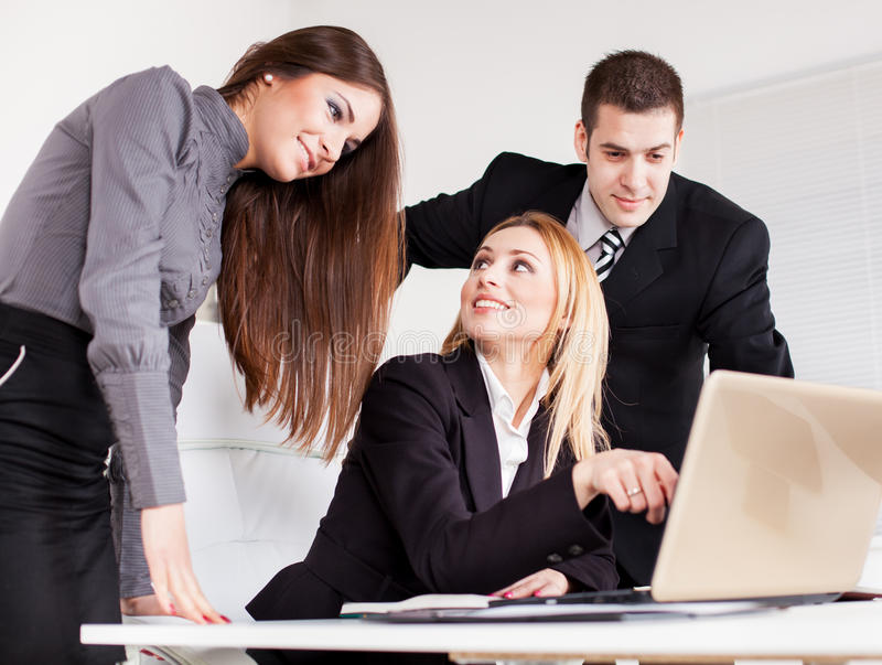 Business Team. Happy Business women showing her colleagues project at laptop in the office stock photos