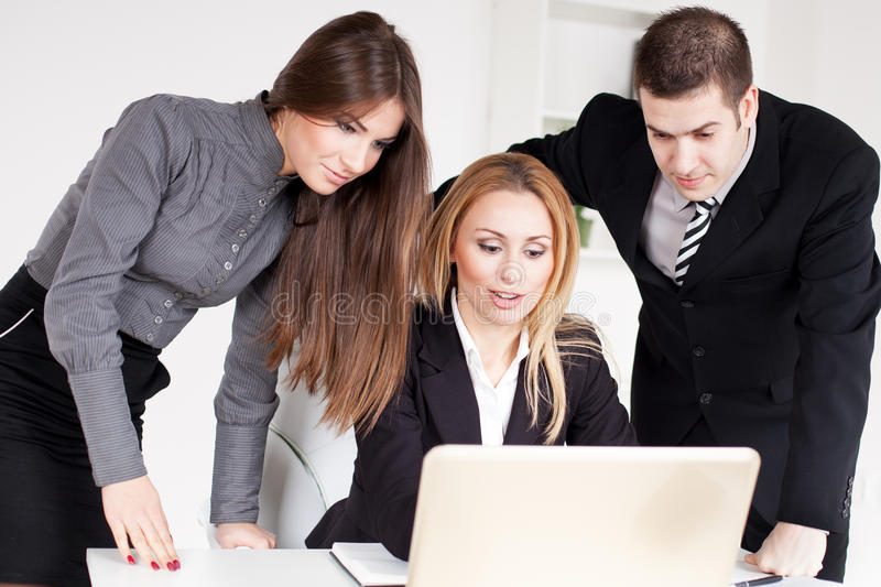 Business Team. Happy Business women showing her colleagues project at laptop in the office stock image