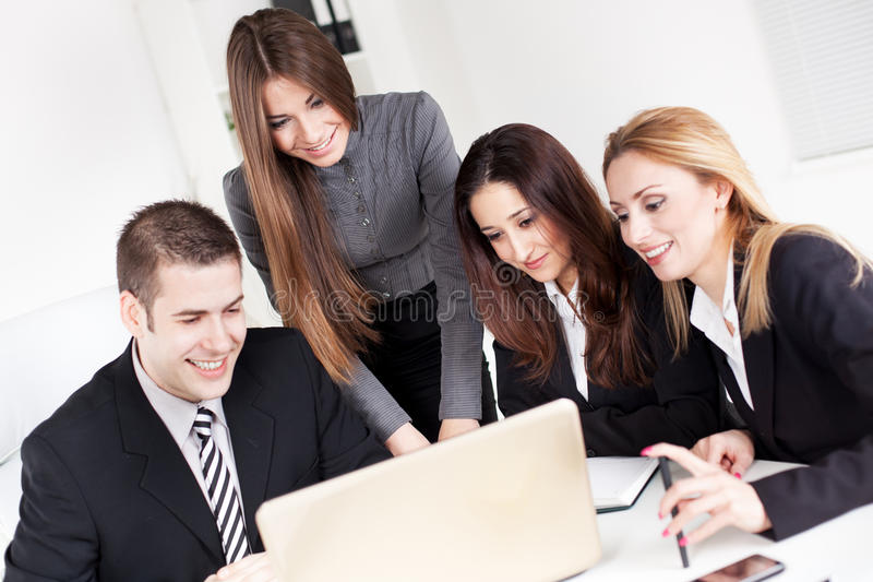Business Team. Happy Business women showing her colleagues project at laptop in the office stock photo