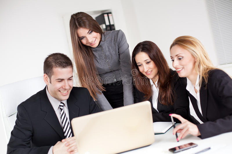 Business Team. Happy young Business women showing her colleagues project at laptop in the office stock photos