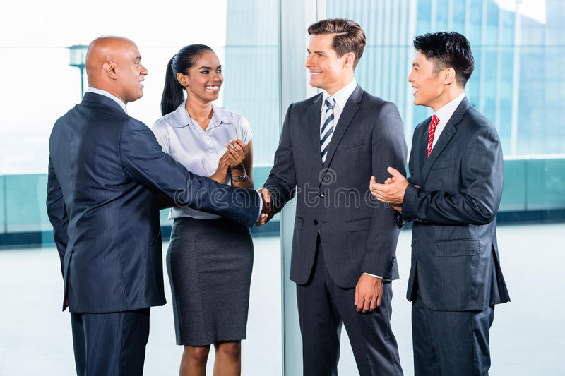 Business team having agreement and handshake. Diversity business team concluding contract with handshake in front of city skyline stock photography