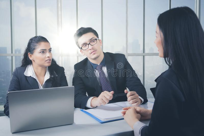 Business team having a discussion while working on laptop computer stock photography