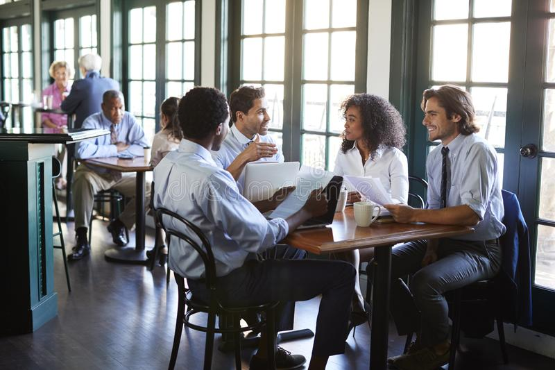 Business Team Having Informal Meeting Around Table In Coffee Shop stock photo
