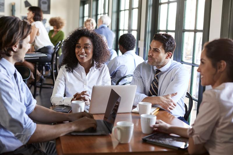 Business Team Having Informal Meeting Around Table In Coffee Shop royalty free stock photography