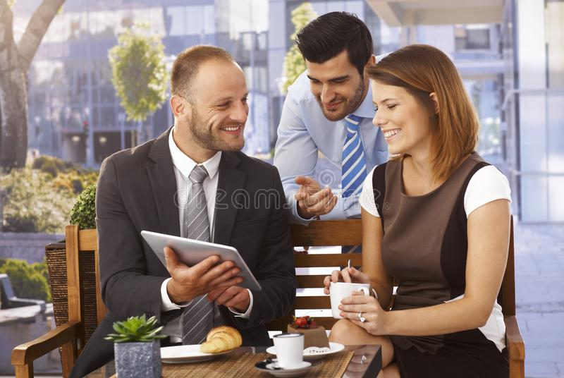 Business team having outdoor meeting using tablet stock photography