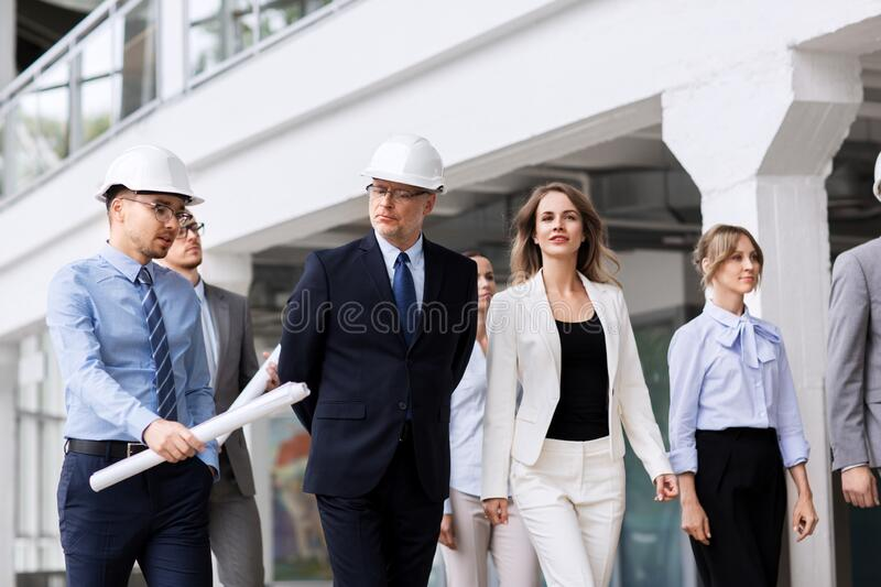 Business team in helmets walking along office stock photography
